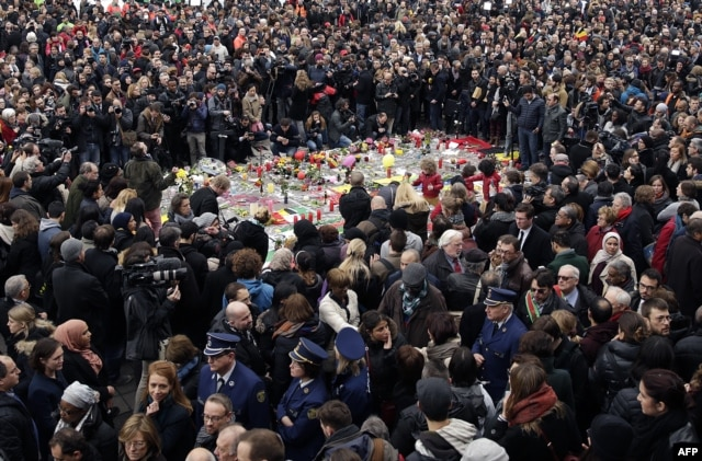 People hold a minute of silence around a makeshift memorial at Place de la Bourse in Brussels on March 23.