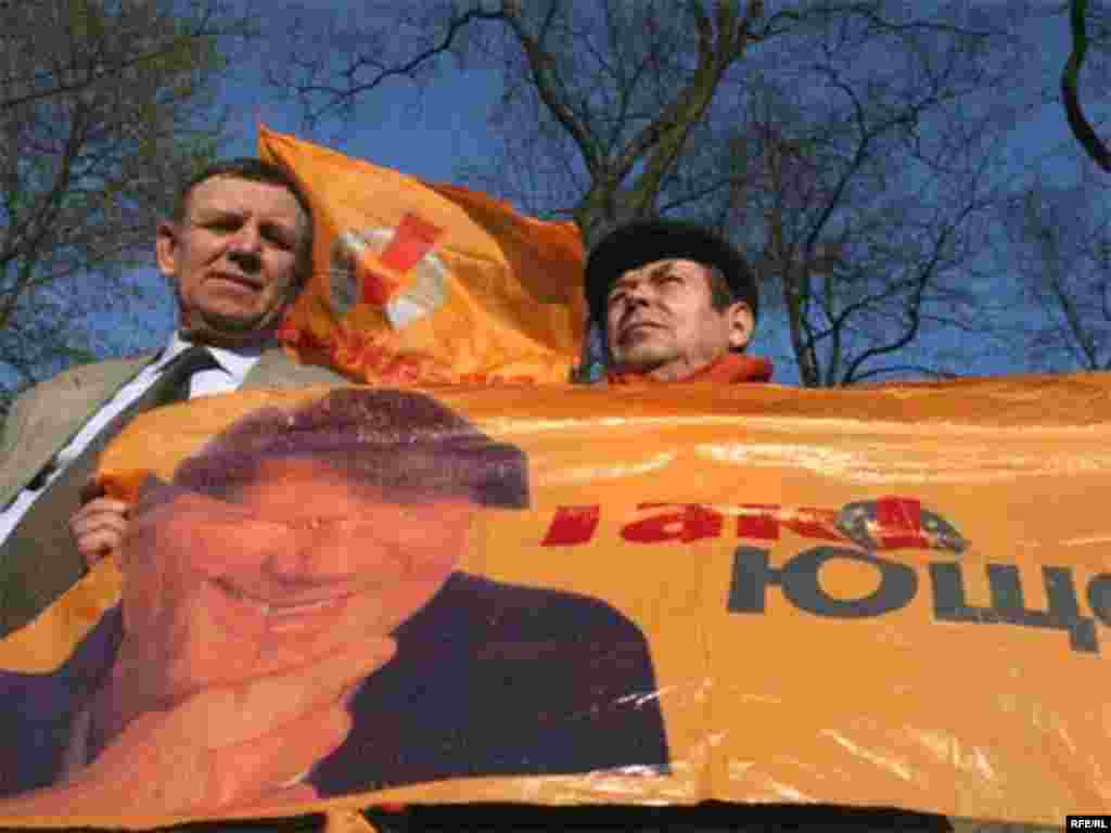 Orange Vs. Blue - Two demonstrators at the pro-presdential opposition rally in Kyiv on April 11 stand over a banner depicting President Viktor Yushchenko. (photo: RFE/RL)
