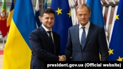Volodymyr Zelenskiy (left) and Donald Tusk shake hands in Brussels on June 5.