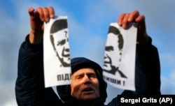 "A demonstrator holds a torn portrait of then-Ukrainian President Viktor Yanukovych and shouts ""Coward!"" at a rally on November 29."