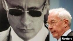 Колишній прем'єр-міністр України Микола Азаров проходить повз портрет президента Росії Володимира Путіна, Москва, 4 лютого 2015 року
