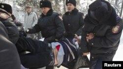 Полицейлер қарсылық жиынына келген адамды әкетіп барады. Алматы, 25 ақпан 2012 жыл.