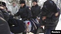 Полицейлер қарсылық акциясына қатысқан адамды әкетіп барады. Алматы, 25 ақпан 2012 жыл.
