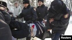 Полицейлер үкіметке наразылық жиынына шыққан белсендіні әкетіп барады. Алматы, 25 ақпан 2012 жыл.