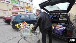 Мужчына загружае машыну таварамі, набытымі ў польскім супэрмаркеце