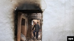 An ethnic Uzbek man walks through the ruins of his house, which was destroyed during ethnic clashes in Osh, on June 17.