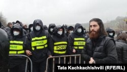აქციის მონაწილე პოლიციის კორდონთან. გუმათი