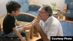 بوسه نوریزاد بر پای کودکی که در خانوادهای بهایی متولد شده و پدر و مادرش زندانی هستند.