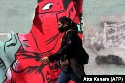 Женщина в маске идет по улице Тегерана. Иран, 13 апреля 2020 года.