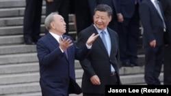 Лидер Китая Си Цзиньпин (справа) приветствует прибывшего с визитом в Пекин президента Казахстана Нурсултана Назарбаева. 7 июня 2018 года.