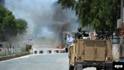 Smoke billows from the scene where suspected militants attacked the state-run RTA TV station in Jalalabad on May 17.