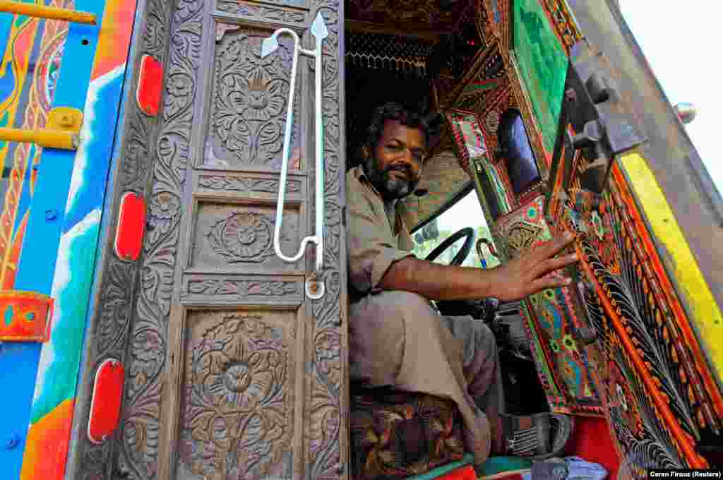 "A driver in Faisalabad shows off the luridly decorated cab of his truck. As well as being a means to show off a driver's ""personality,"" truck decorations have one basis in business logic."