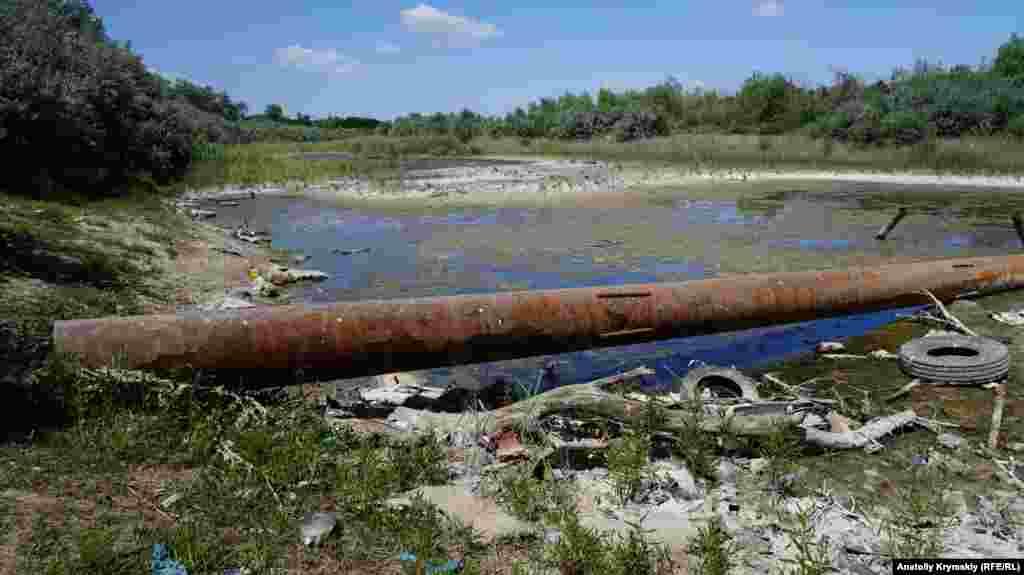 На дне высохшего канала остались небольшие болотца с накопившимся мусором