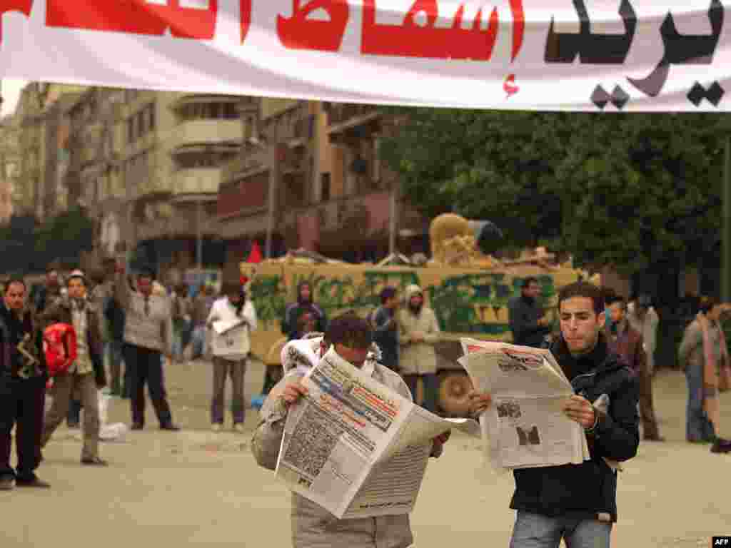 "Protesters read newspapers under a banner reading ""People Want The Regime To Fall"" in Tahrir Square on February 5."