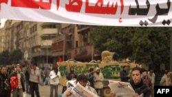 """Демонстранты читают газеты с требованиями об отставке президента Хосни Мубарака. Площадь """"Тахрир"""", Каир, Египет. 5 февраля 2011 г. AFP."""