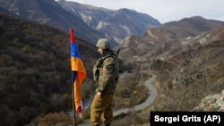 NAGORNO-KARABAKH -- An ethnic Armenian soldier stands guard next to Nagorno-Karabakh's flag atop of the hill near Charektar in at a new border with Kelbajar district turned over to Azerbaijan, November 25, 2020.
