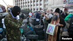 Sveštenik daje blagoslov proruskim separatistima, Donjeck, 24. april 2014.