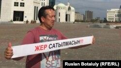Гражданский активист Галымбек Акулбеков проводит акцию протеста. Астана, 20 апреля 2016 года.