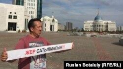 Активист Галымбек Акулбеков держит баннер, призывающий не продавать землю. Астана, 20 апреля 2016 года. Иллюстративное фото.