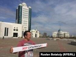 Активист Галымбек Акулбеков стоит в центре Астаны с плакатом, призывающим не продавать землю. Астана, 20 апреля 2016 года.