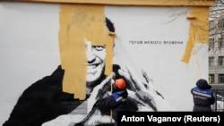 Рабочие закрашивают граффити с изображением Алексея Навального. Санкт-Петербург, 28 апреля 2021 года