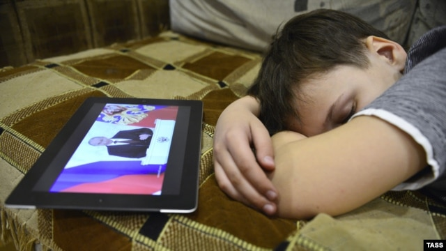 A boy in Vladivostok sleeps as his tablet computer shows Vladimir Putin's annual state-of-the-nation address on December 12.