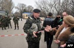 Женщина разговаривает с украинским военным в Керчи, 4 марта 2014 года