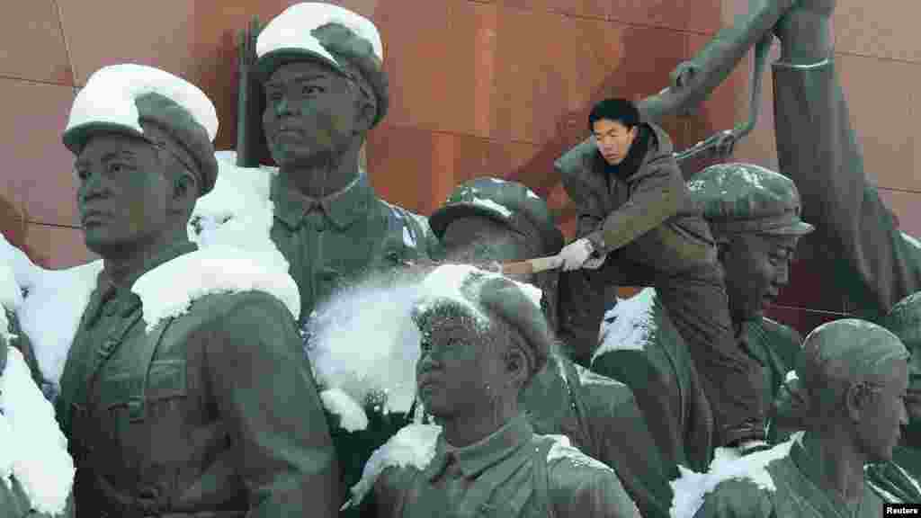 A man brushes snow off the top of a monument in Pyongyang, North Korea. (Reuters/Kyodo)