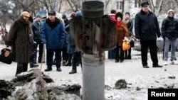 Люди розглядають залишки ракетного снаряду на вулиці Краматорська. 10 лютого 2015 року