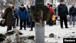 Жители Краматорска рассматривают снаряд, упавший в центре города