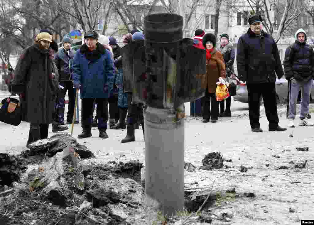 People look at the remains of a rocket shell on a street in the town of Kramatorsk, eastern Ukraine, on February 10. (Reuters/Gleb Garanich)