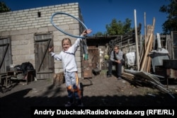 Toma, now 6, plays in the yard of her house, from where she can see Donetsk: Frontline positions are just a few hundred meters away.