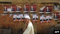 Президенттікке кандидат Мухаммед Морси мен Абдел Монейм Абул Фотухтың сайлау жарнамалары маңынан өтіп бара жатқан адам. Каир, 18 мамыр 2012 жыл. (Көрнекі сурет)