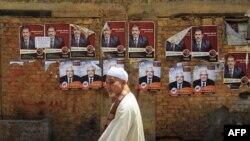Мужчина идет мимо предвыборных плакатов кандидатов в президенты. Каир, 18 мая 2012 года.