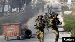Израильские солдаты бегут во время столкновения с палестинскими демонстрантами. Рамаллах, 25 июля 2014 года.