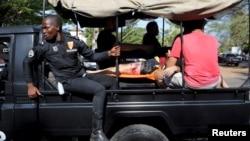 Сили безпеки везуть постраждалого через атаки у Кот-д'Івуарі, 13 березня 2016 року