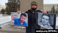 A activist holds up photos of Dulat Agadil (left) and his son Zhanbolat.