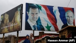 Posters of Syrian President Bashar Assad and Russian President Vladimir Putin in Aleppo, Syria, Thursday, Jan. 18, 2018