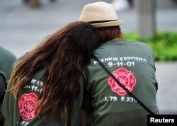 ABŞ - İnsanlar Dünya Ticarət Mərkəzində terror aktından sonra rəşadət göstərmiş xilasediciləri yad etmək üçün paltarlarına onların təşkilatının emblemini vurublar, 11 sentyabr, 2013, New York