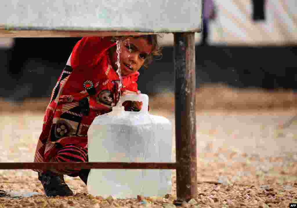 An Iraqi refugee girl, who fled the Iraqi city of Mosul due to the fighting between government forces and Islamic State (IS) militants, fills a container with water at a UN-run refugee camp in Syria's Hasakeh Province. (AFP/Delil Souleiman)