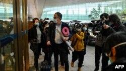 A WHO vizsgálócsoportjának tagjai megérkeznek a Tianhe nemzetközi repülőtérre Vuhanban végzett vizsgálataik után, 2021. február 10-én