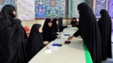 Voters register to cast their ballots during parliamentary elections at a polling station in Tehran on February 21.