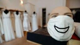 Модельер Фридерике Йорциг надевает маску на манекен в своем магазине в Берлине.