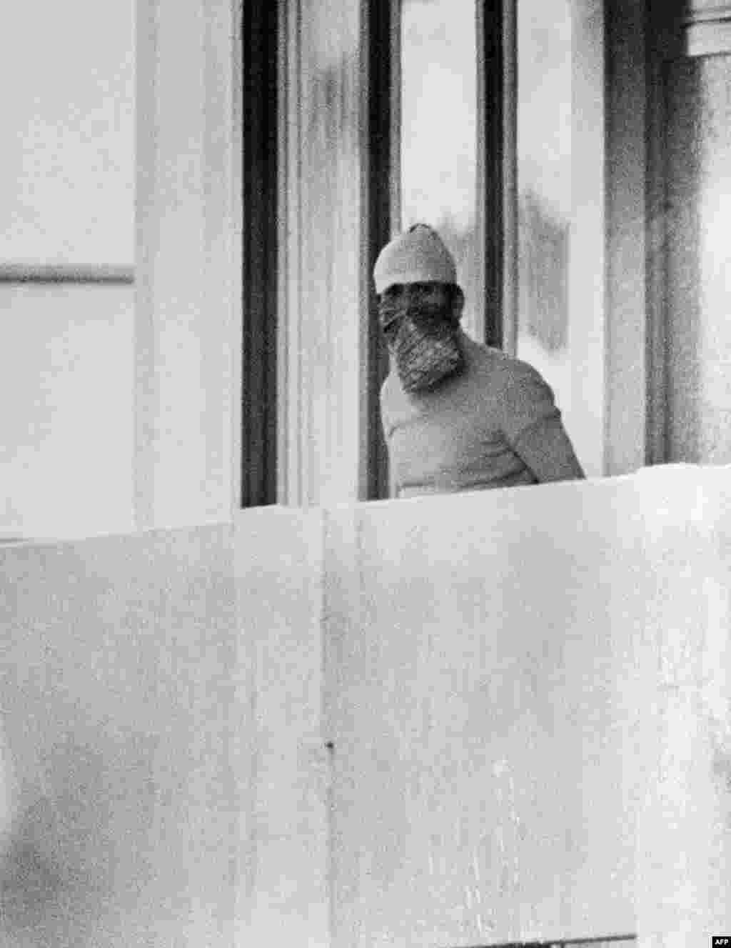 A Palestinian hostage taker appears on the balcony of an Israeli apartment at the Olympic village.