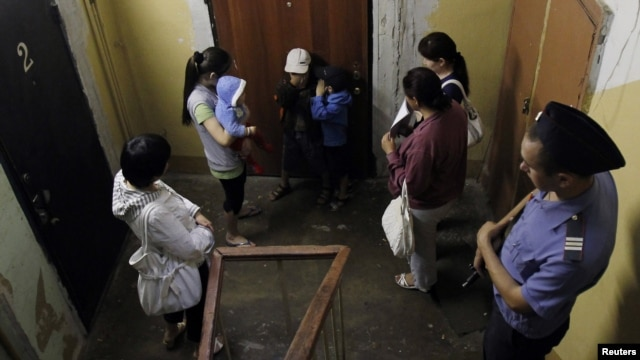 Kyrgyz women and their children are detained during a police raid on migrant workers in downtown Moscow last year.