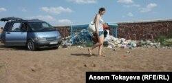 Девушка идет по берегу водохранилища Коянды близ Астаны.