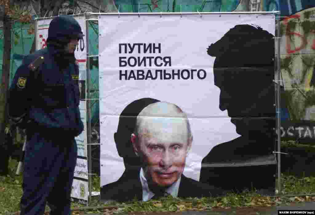A police officer stands near a placard depicting Russian opposition leader and anticorruption blogger Aleksei Navalny's shadow (right) bending over President Vladimir Putin in Kirov. (epa/Maksim Shipenkov)