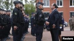Француз президенти Франсуа Олланд Каледеги качкындар лагериндеги тартип сакчылары менен жолукту.