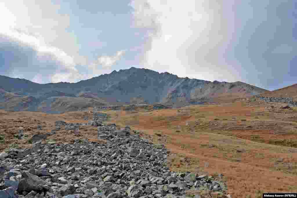 На этом фото – долина ниже Кыземшека. На камнях, которые тянутся вниз полосами, множество наскальных рисунков, датируемых эпохами бронзы, раннего железного века и первыми десятью веками нашей эры. Считается, что скопление петроглифов в этом районе Казахстана обнаружила 20 августа 2010 года группа туристов из пяти человек.