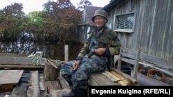 Алексей Воронин рядом со своим затопленным домом в разгар наводнения.